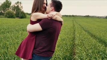una pareja romántica dando vueltas, besándose, riendo y divirtiéndose juntos en un campo verde. cámara lenta, tiro steadicam video