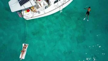 aerial slow motion video of people relaxing on a sailboat