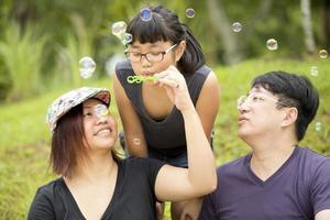 Joven asiática jugando a soplar burbujas en el parque de vinculación