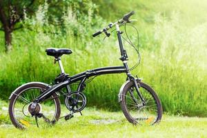 Black folding bicycle in grass