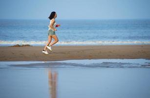 Woman running on beach at sunset.