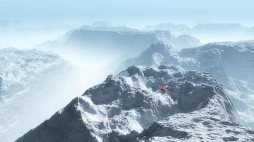 avión privado rojo sobre paisaje de montaña de invierno brumoso. foto