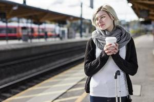 mujer tomando café mientras espera el tren