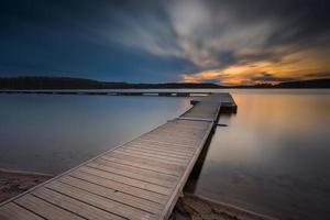 Beautiful long exposure lake with jetty at sunset. photo
