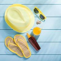 Summer accessories on blue wooden background top view