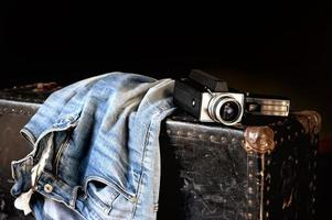 Pair of jeans and movie camera on suitcase photo