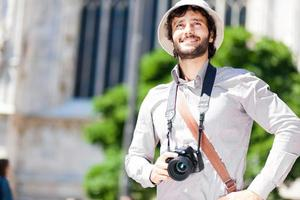 Happy tourist holding a camera photo