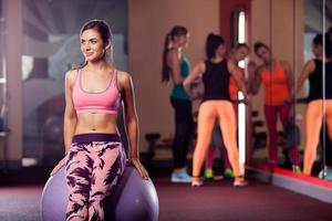 young adult sporty woman posing on fitball