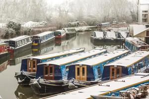 Canal boats seem to huddle in the snow