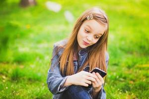 portrait of smiling teenage girl with mobile phone photo