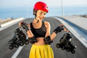 mujer deportiva con rodillos en la carretera