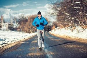 Muscular athlete man jogging outdoor on snow, training for practice