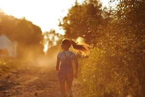 garota feliz correndo por uma estrada rural