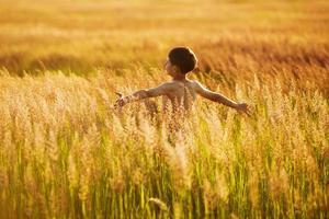 menino feliz correndo na grama em uma noite de verão