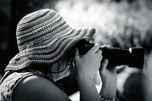mujer es fotógrafa usando una cámara réflex digital
