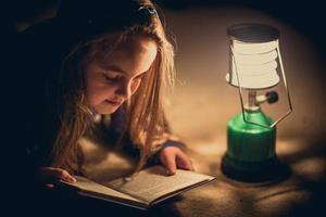 niña leyendo un libro en la lámpara de iluminación