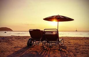 Vintage stylized beach chairs and umbrella at sunset.
