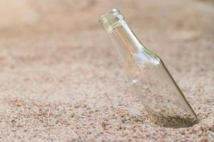 Empty glass bottle in the sand