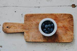 Bowl of blueberries on cutting board