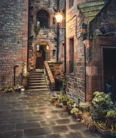Illuminated lamp post above stone pathway in Dean Village, Scotland