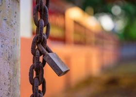 Viejo candado oxidado y cadena en la puerta