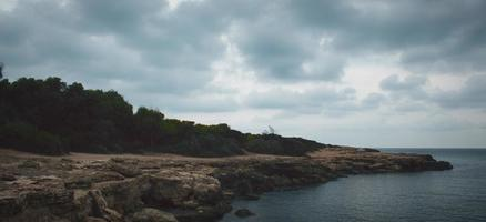 Clouds over a rocky seashore