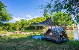Camping y carpa en la naturaleza en el río.