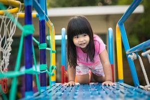 Asian little girl enjoys playing at the playground