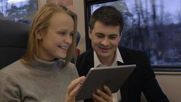 Amigos riendo mientras usan la almohadilla en el tren