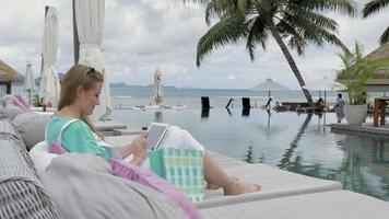Woman in luxury hotel using digital tablet during vacation, outdoors.