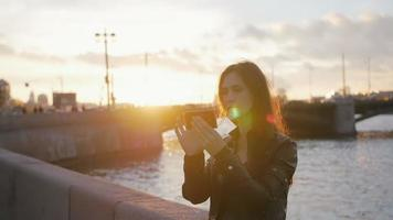 ein Mädchen, das Selfie macht, während die Sonne an einem wunderbaren Ort untergeht. belebte Straße, eine Brücke, ein Fluss im Hintergrund, langsam mo