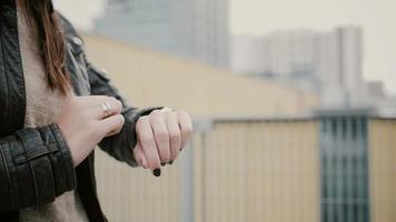 mulher usando seu smartwatch touchscreen em pé no telhado e depois vai embora. close up das mãos. fullhd