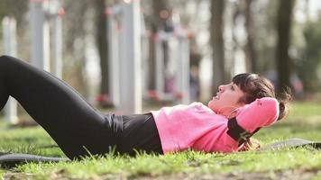 jovem fazendo exercícios abdominais no parque