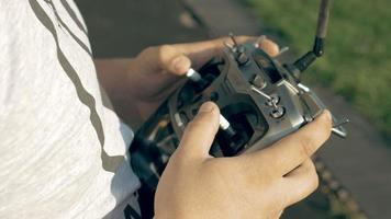 mãos segurando um transmissor controlando drone fpv