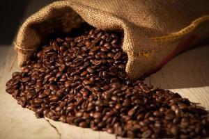 Coffee beans in burlap sack against dark wood photo