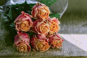 Autumn Ecuador roses on the vintage wooden table