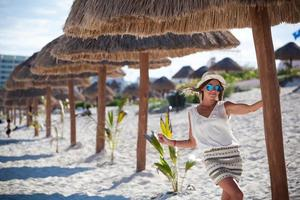 Tanned woman on vacation under thatched hut photo