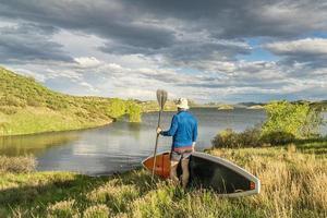 Paddler macho con stand up paddleboard en la orilla del lago cubierto de hierba