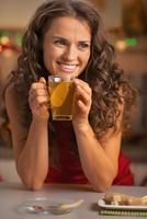 happy young woman drinking ginger tea with lemon photo