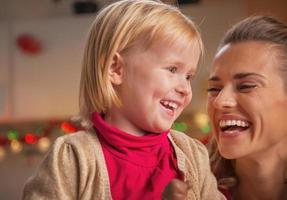 Portrait of mother and baby in christmas decorated kitchen photo