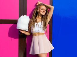 hermosa mujer joven en una falda rosa posando junto a la pared foto