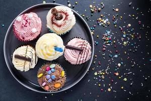 Cupcakes vibrantes en placa sobre fondo oscuro foto