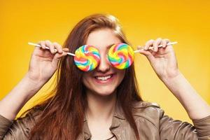 Happy young girl with lollipop on a yellow photo