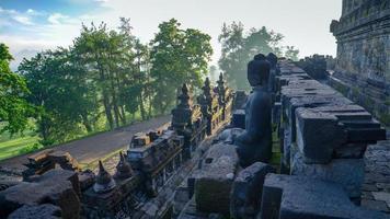 Buddha sitting on rocks in the sun waiting photo