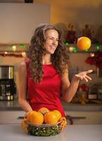 Happy young woman throwing up orange in christmas decorated kitchen photo