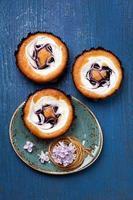 tortas con bayas y crema sobre fondo azul foto