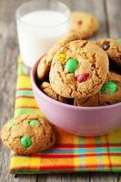 Cookies with colorful candy in bowl on grey wooden background photo