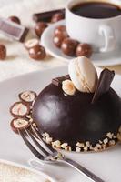 Round chocolate cake with nuts on a plate close-up,  vertical