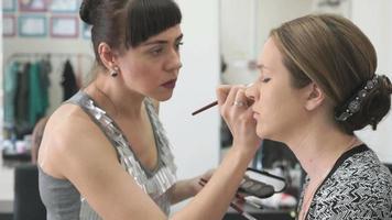 maquiador fazendo maquiagem para jovem modelo