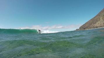 Cámara lenta bajo el agua: hombre surfista navegando con cámara de paso de olas grandes